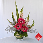 Arrangement triangulaire gerberas roses.